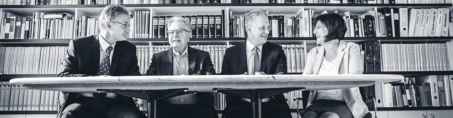 Rechtsanwälte der Anwaltskanzlei Schnorrenberg Oelbermann vor einen Bücherregal