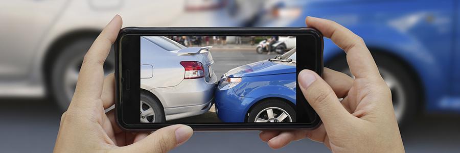 Zwei Hände machen mit Handy Foto von Autounfall